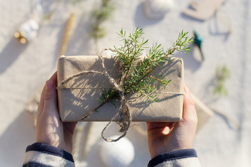 gift in kraft packaging, tied with linen rope, decorated with juniper twig in the hands of a child in the sunlight on the background of Christmas decorations