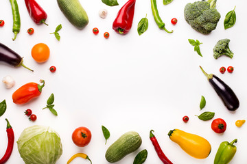 Frame of colored organic vegetables on white