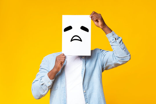 African american guy hiding face behind paper with sad emoticon