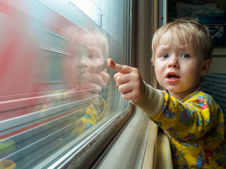 Mom, look - the train! A bright, cute three-year-old boy riding a train looks out the window, behind which a dull landscape sweeps through.