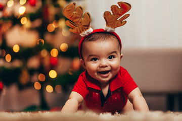 Cute baby boy wearing reindeer antlers crawling on floor over Christmas lights. Looking at camera. Holiday season.