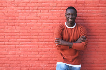African Young Man Smiling With Red Wall In Background