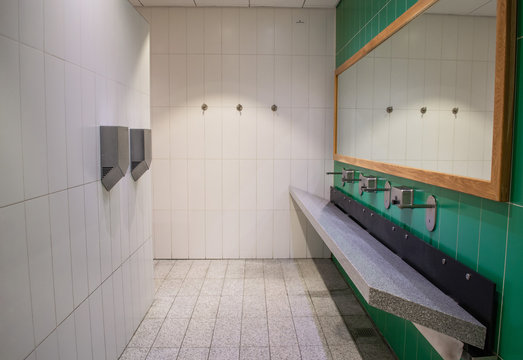 Modern public toilet in white and green with large mirror, sloping stone sink, touch faucets and metal powerful hand dryers