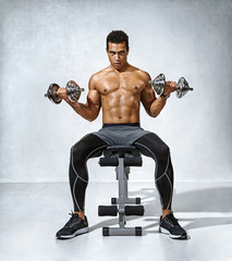 Man doing exercises with dumbbells on bench. Photo of muscular fitness model naked torso on grey background. Strength and motivation