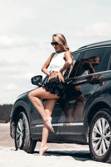 Charming sexy woman on tiptoe leaning on car on road