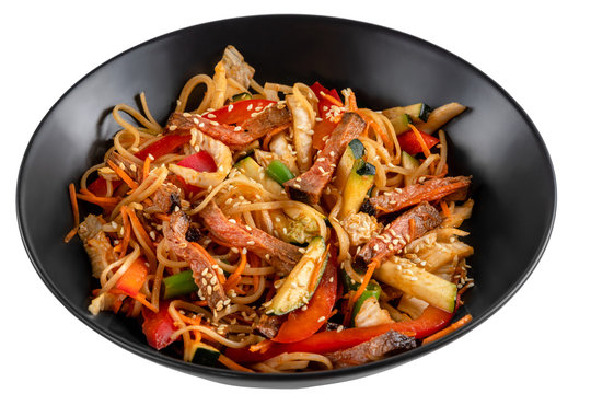 Sliced beef, noodles in sauce, vegetables and sesame seeds in a black plate isolated on white background, side view