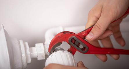 heater repair hand on white wall
