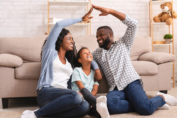 African couple making symbolic roof of hands above little girl
