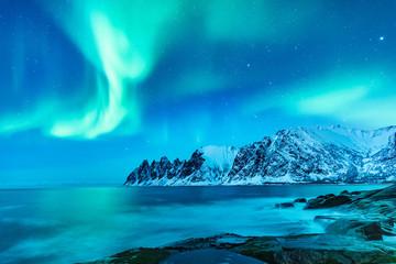 Vivid Northern lights during polar night on Lofoten Islands in Norway. Epic scene of dancing aurora borealis in the night sky over jagged mountain ridge and Arctic ocean on island Senja, polar circle.
