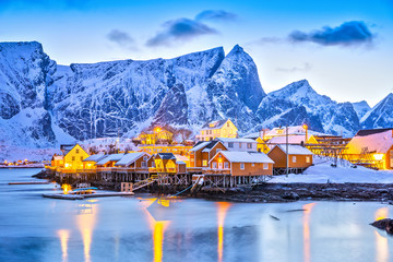 Sakrisoy village on Lofoten Islands in Norway, beautiful twilight view with street lamp reflections during winter season. Blue color in nature.