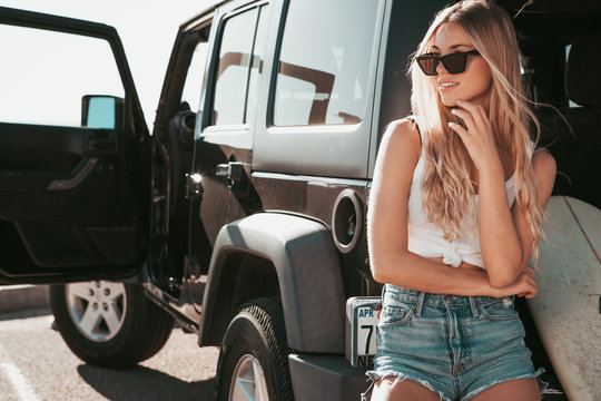 surfer girl sitting at a car with surfboard. california lifestyle