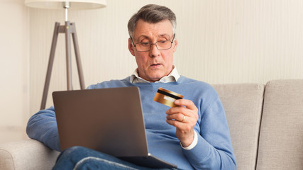 Elderly Man Holding Credit Card And Laptop Sitting On Couch