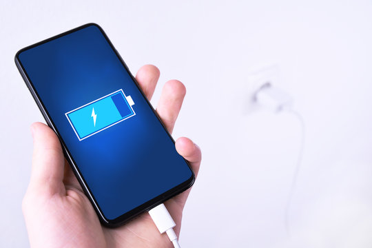 A human ,man hand puts charge the battery mobile smart phone, cellphone ,mobile on the white background with a socket in the frame.