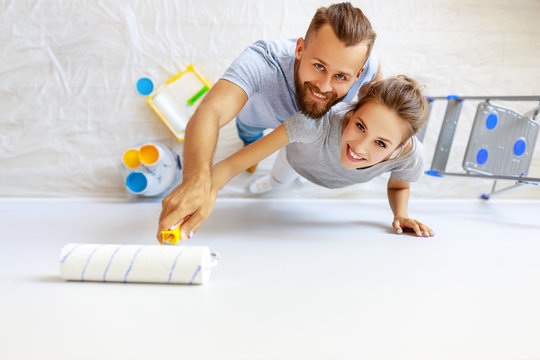 young happy couple is repairing and painting   wall at home