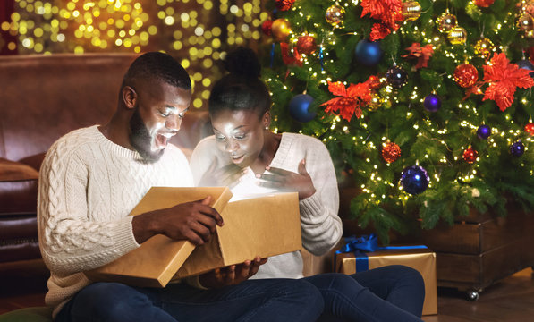 Dazed black couple opening xmas gift box in living room near Christmas tree
