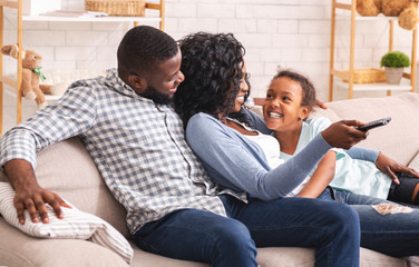 Joyful black family of three relaxing on sofa at home