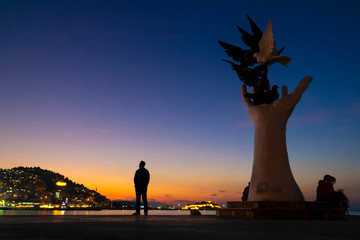 Hand Statue that represent Peace at sunset. Kusadasi is populer tourism destination in Turkey. Silhouette of a man is looking across.