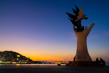 Hand Statue that represent Peace at sunset. Kusadasi is populer tourism destination in Turkey..