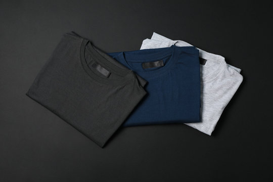 Folded multicolored t-shirts on black background, space for text