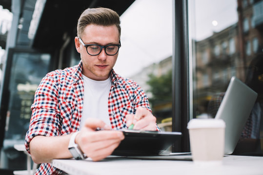 Man writing on clipboard sitting with laptop in cafe