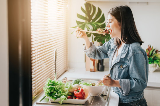Happy woman eating healthy fresh vegetables salad in kitchen
