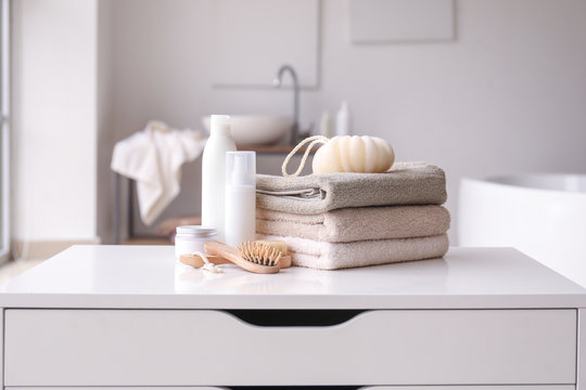 Stack of towels, cosmetics, loofah and brushes on table in bathroom