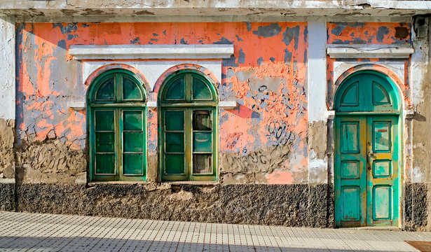 Old colorful house with pink walls and green doors, a detail of beutiful vintage architecture.
