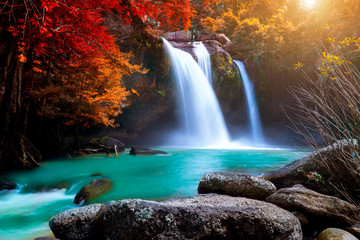 Papiers peints Automne The amazing colorful waterfall in autumn forest blue water and colorful rain forest.