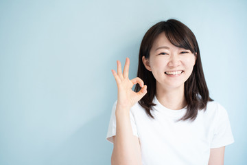 Young woman shoing OK gesture against light blue background
