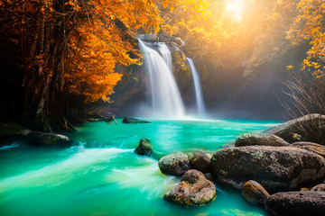 The amazing colorful waterfall in autumn forest blue water and colorful rain forest.