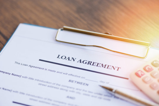 loan agreement application form with pen and calculator on paper financial help - financial loan negotiation for lender and borrower on business document mortgage loan approval