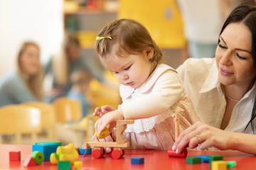 Child building blocks with a teacher in the nursery