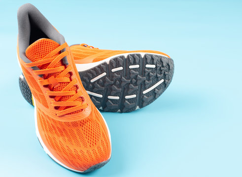 Orange sport shoes on a blue background. Concept for good health.