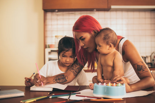 Happy young mother and kids spending time together at home.