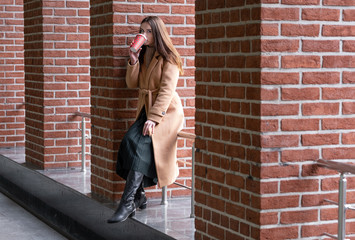 a young woman sits against a brick wall and drinks hot coffee from a cup. on young girl autumn beige overcoat.