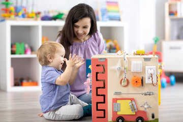 Child with teacher playing educational toys Kid toddler develops motor skills.