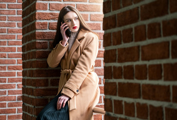 a young woman sits against a brick wall and talks on the phone. on young girl autumn beige overcoat. the woman looks away. the concept of communication and cellular communication
