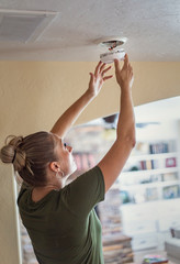 Changing the battery on a smoke alarm in an interior of a home. Woman standing on a step ladder and fixing the smoke alarm.