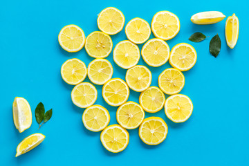 Lemon slices and leaves pattern on blue background top view