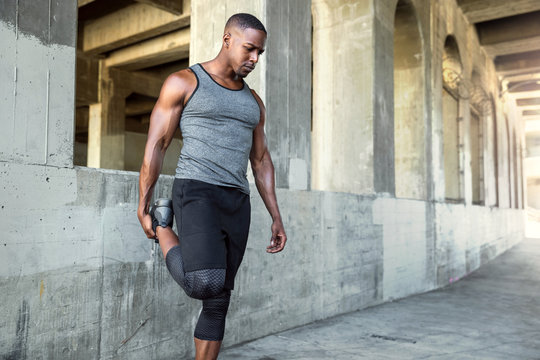 Lifestyle portrait of a male athlete with strong muscular body, stretching legs before running, urban exercise