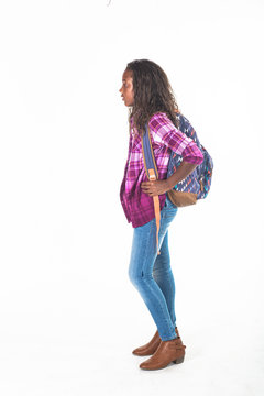African American school girl isolated on white background. Wearing a backpack and a plaid jacket and ready to go to school. side view