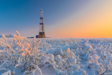 In a winter snow-covered tundra, a well is being drilled at an oil and gas field. Polar day. Beautiful sky. The drilling rig is covered in snow.