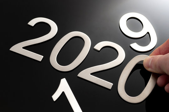 Happy new year conceptual idea with hand changing the last to digits from the number 2019 to become 2020