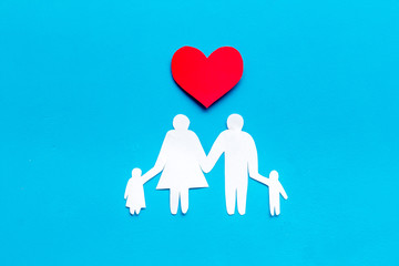 Happy family concept. Heart icon near mom, dad and childrens cutout on blue background top view copy space