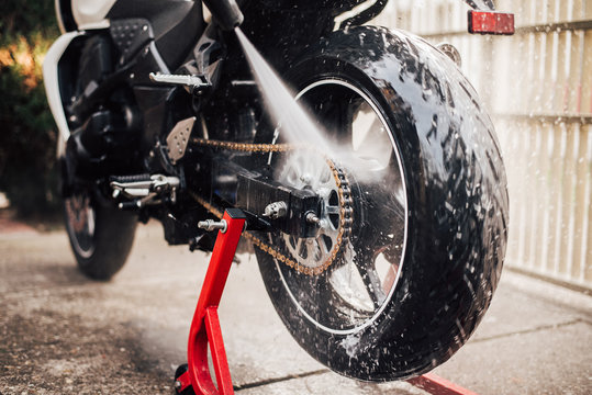 Washing motorcycle chain with high pressure jet, close-up.