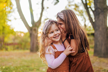 Portrait of two little sisters in a park, whispering secrets.