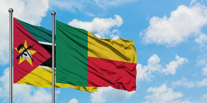 Mozambique and Benin flag waving in the wind against white cloudy blue sky together. Diplomacy concept, international relations.