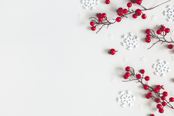 Christmas or winter composition. Snowflakes and red berries on gray background. Christmas, winter,...