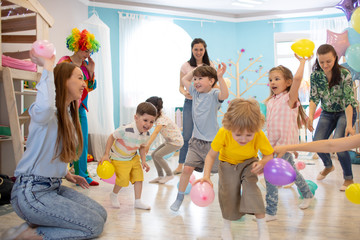 Happy children and their parents entertain and have fun with color balloons on birthday party