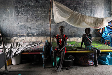 Displaced girls sit on a bed in a classroom, in a school now occupied by IDPs after heavy rains and floods forced hundreds of thousands of people to leave their homes, in the town of Pibor, Boma state